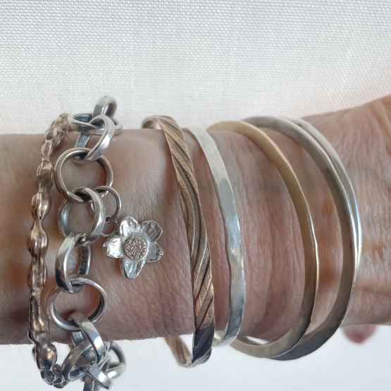 Arm showing a collection of Bangles and Chains in Silver, Gold and Bronze
